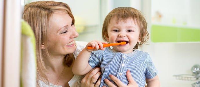 child brushing teeth with mum