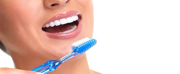 woman brushing teeth with blue brush